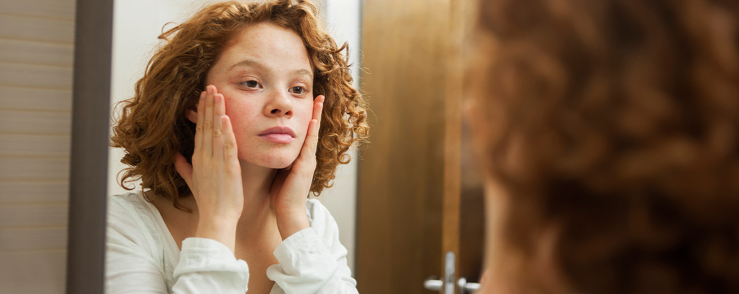Young female adult looking at her face in mirror