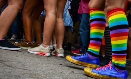 a group of people with only their legs visible, one of the people have rainbow coloured knee-high socks on