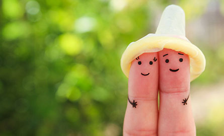 A condom placed on two fingers with smiley faces drawn on the fingers